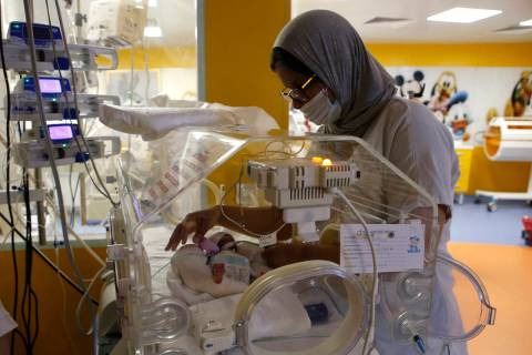 A Moroccan nurse takes care of one of the nine babies protected in an incubator at the maternit ...
