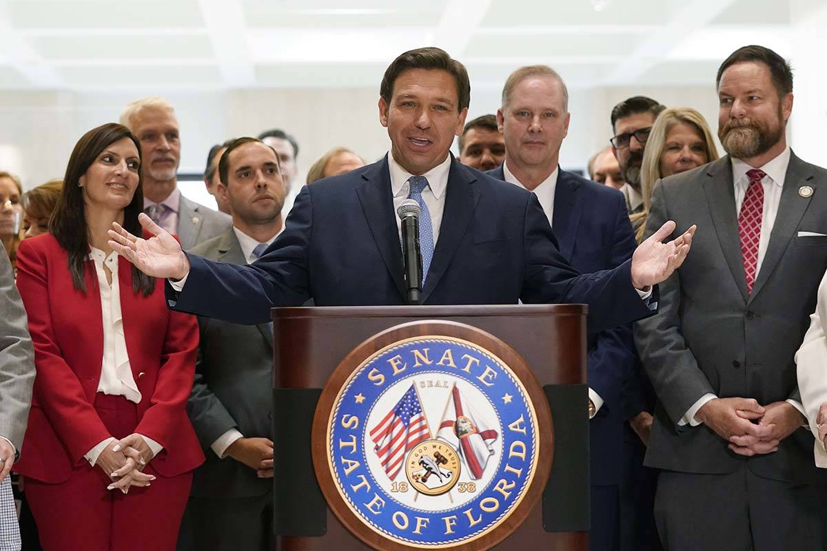Surrounded by lawmakers, Florida Gov.Ron DeSantis speaks at the end of a legislative session, F ...