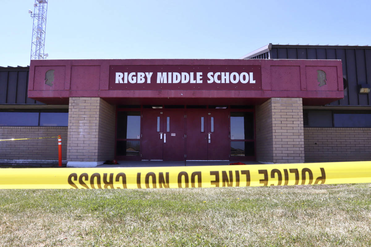 Police tape marks a line outside Rigby Middle School following a shooting there earlier Thursda ...