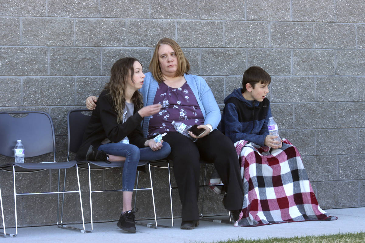A woman and children sit together at the high school where people were evacuated after a shooti ...