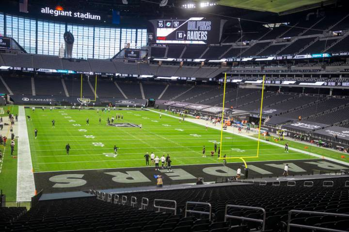 Teams warm up in an empty stadium before an NFL football game between the Raiders and the Miami ...