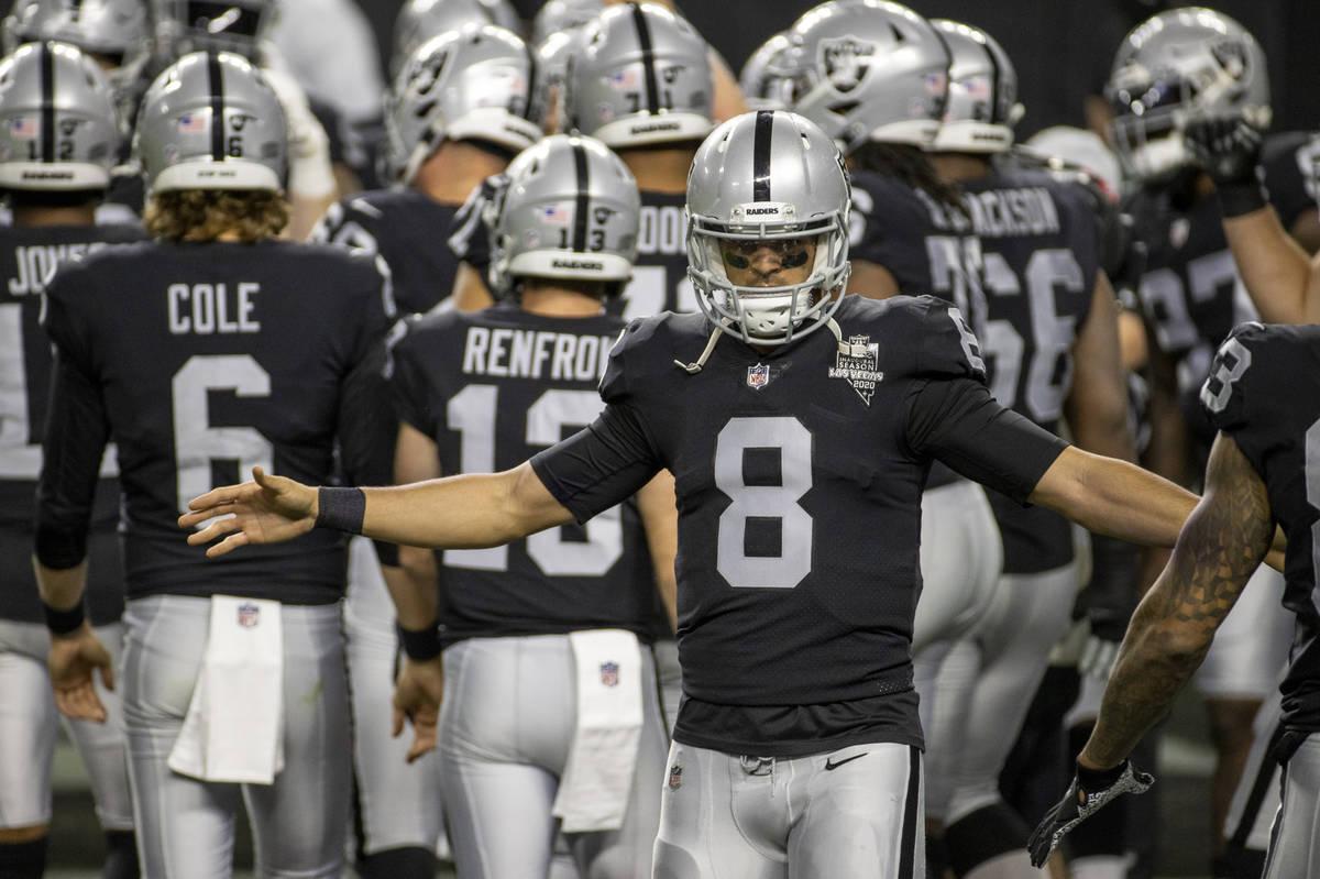 Raiders quarterback Marcus Mariota (8) greets his teammates during warm ups before an NFL footb ...