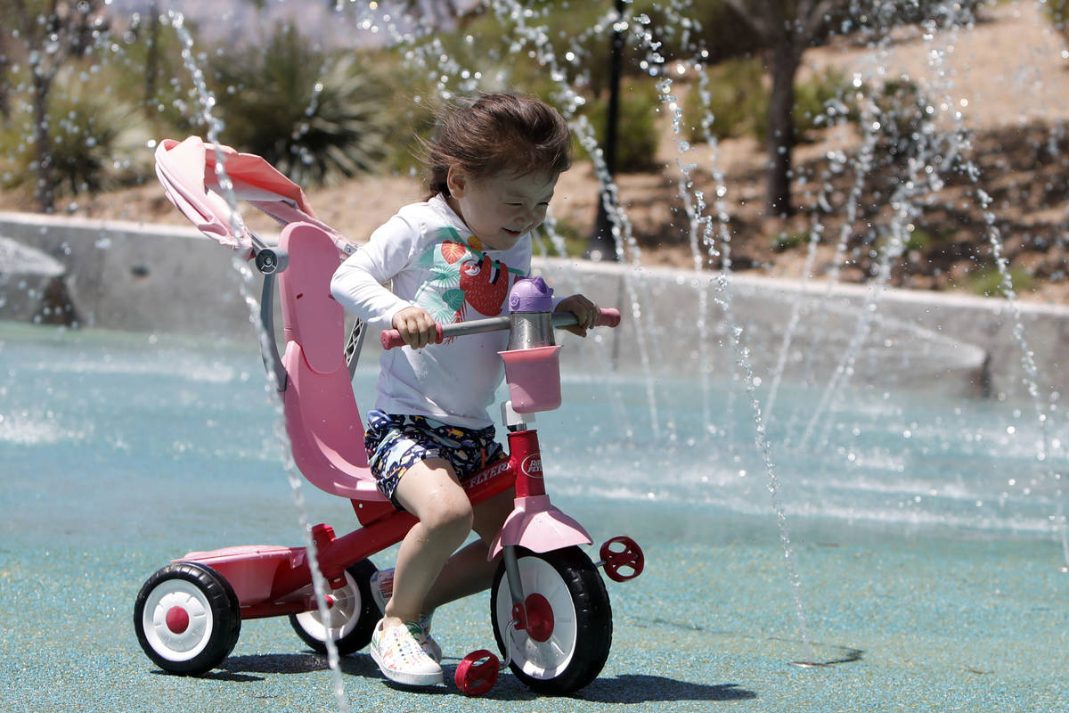 Luna Gyes, 2, of Summerlin rides a bike through the splash pad at Paseos Park in Las Vegas, Sa ...