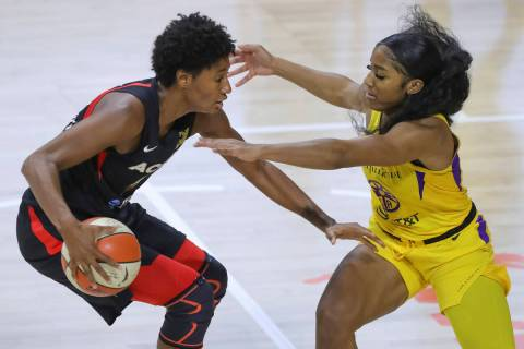 Las Vegas Aces' Angel McCoughtry, left, drives against Los Angeles Sparks' Te'a Cooper during t ...
