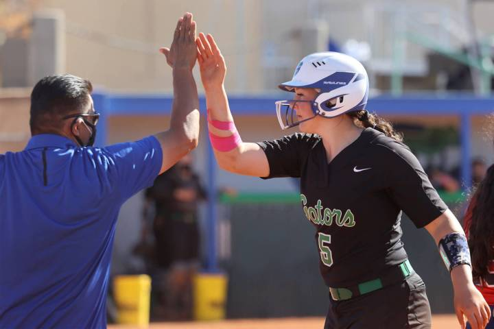 Green Valley's Ava Mearideth (5) high fives coach Tony Perez after a single in the third inning ...
