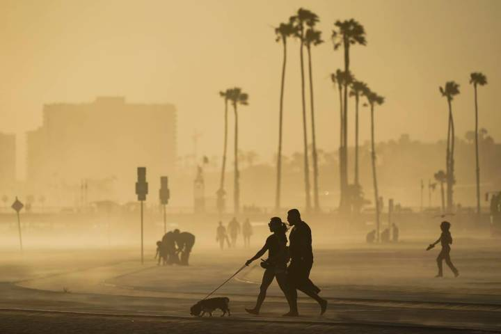 FILE - In this April 18, 2021, file photo, people walk on a beach path as evening winds kick up ...
