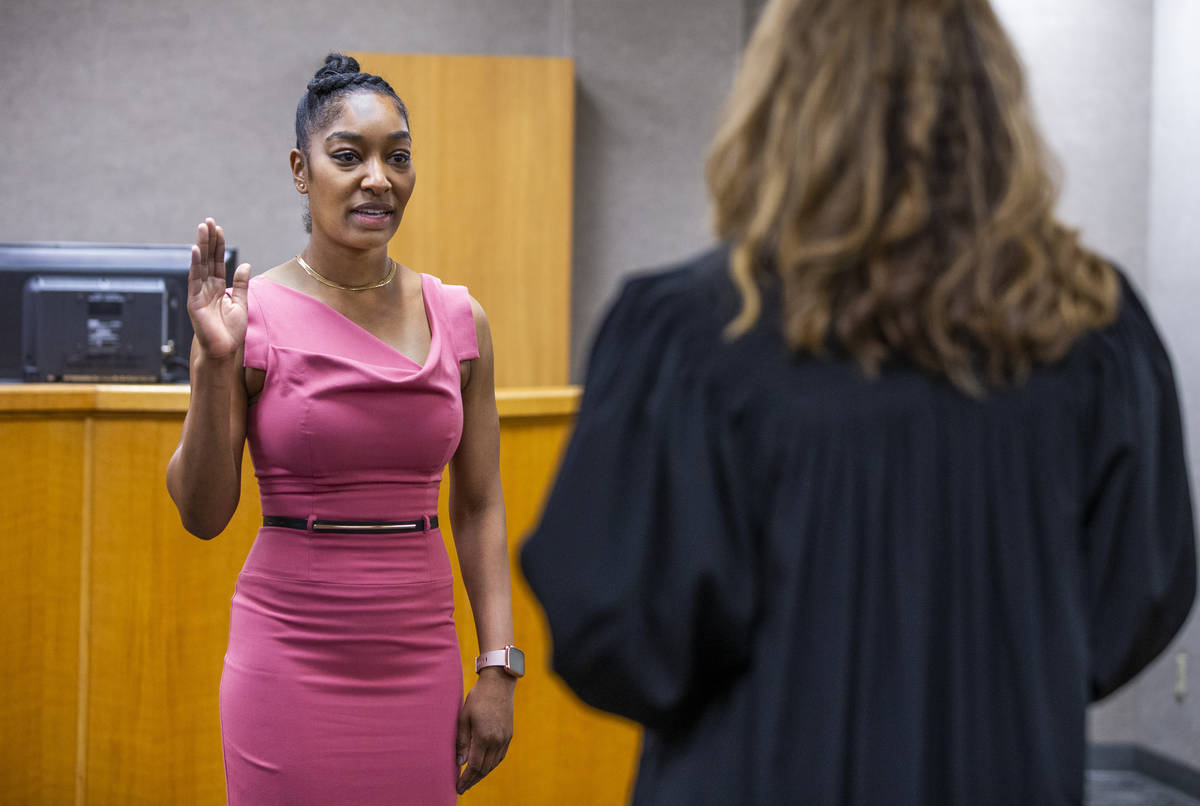 Dominique Bosa-Edwards, left, a former District Court marshal, is sworn in by Judge Veronica M. ...