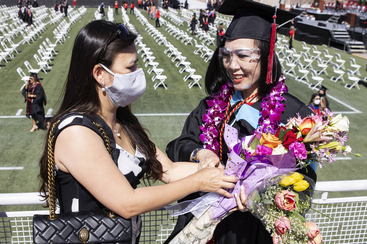 Thuanthi Huynh Tong-Hause, right, receives a bouquet of flowers from her friend Nhung Do after ...