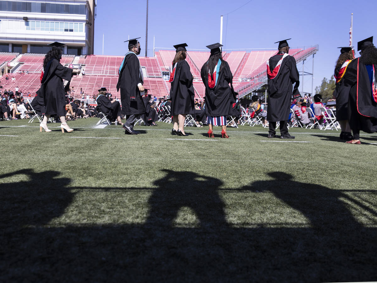 Family members shadows are seen as they take a picture of graduates during the first of several ...