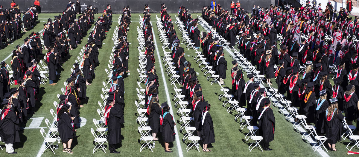 Graduates stand during the National Anthem as they attend the first of several UNLV graduation ...