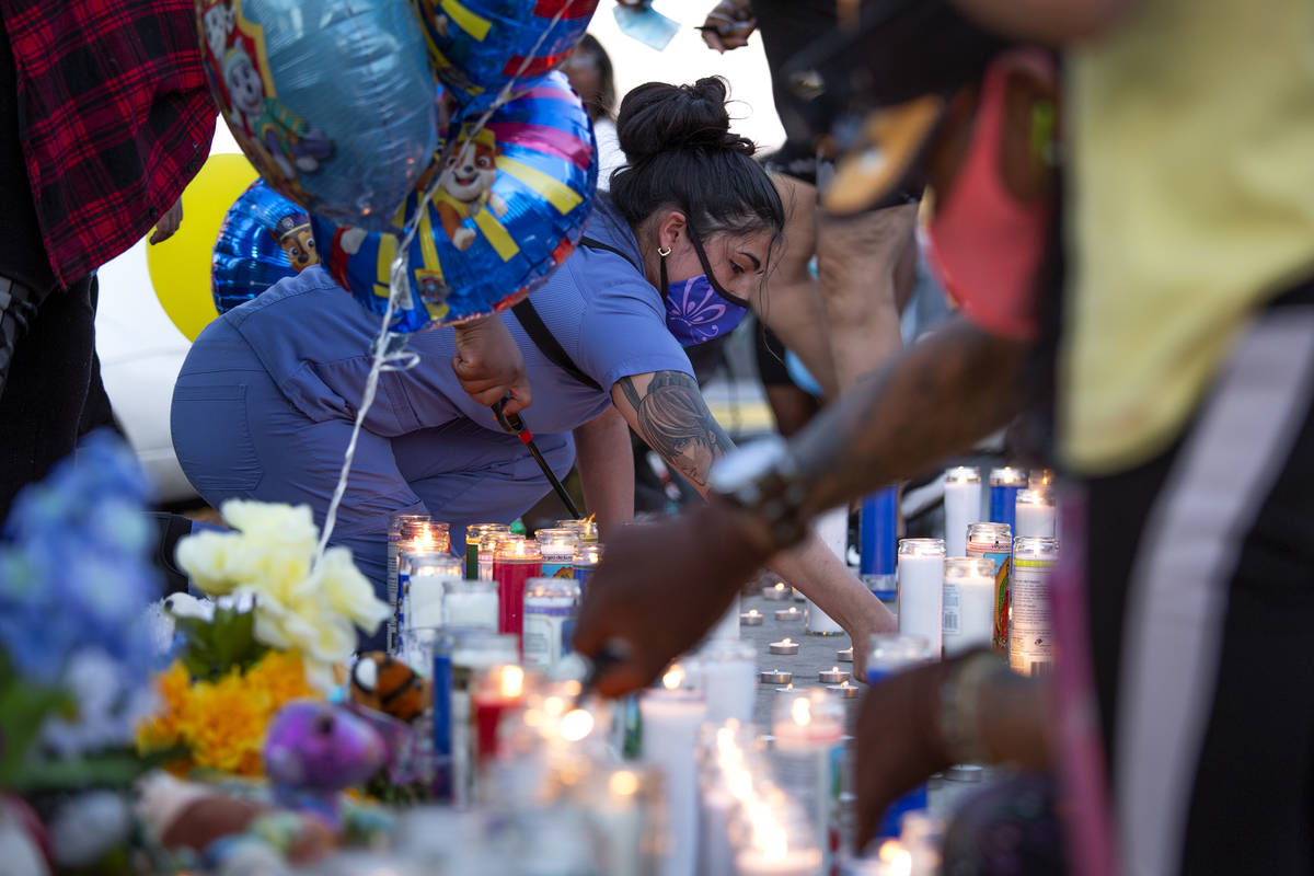 Angel Calderon, center, lights a candle during a vigil for 2-year-old Amari Nicholson outside t ...