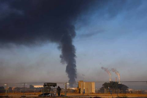 An Israeli soldier stands guard next to an Iron Dome air defense system as smoke rises from an ...