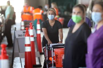 Workers prepare to give shots during a drive-thru COVID-19 vaccine clinic in the Bronze Lot at ...