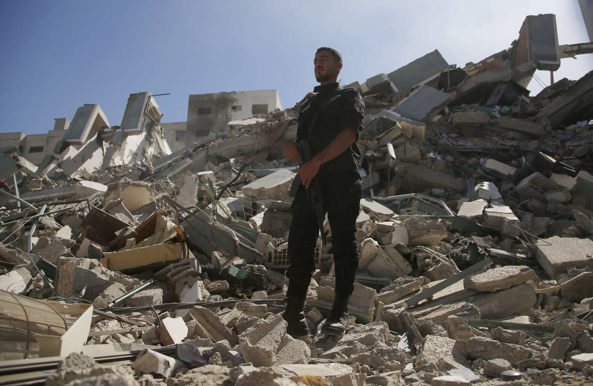 A man stands on rubble from a building housing AP office and other media in Gaza City that was ...