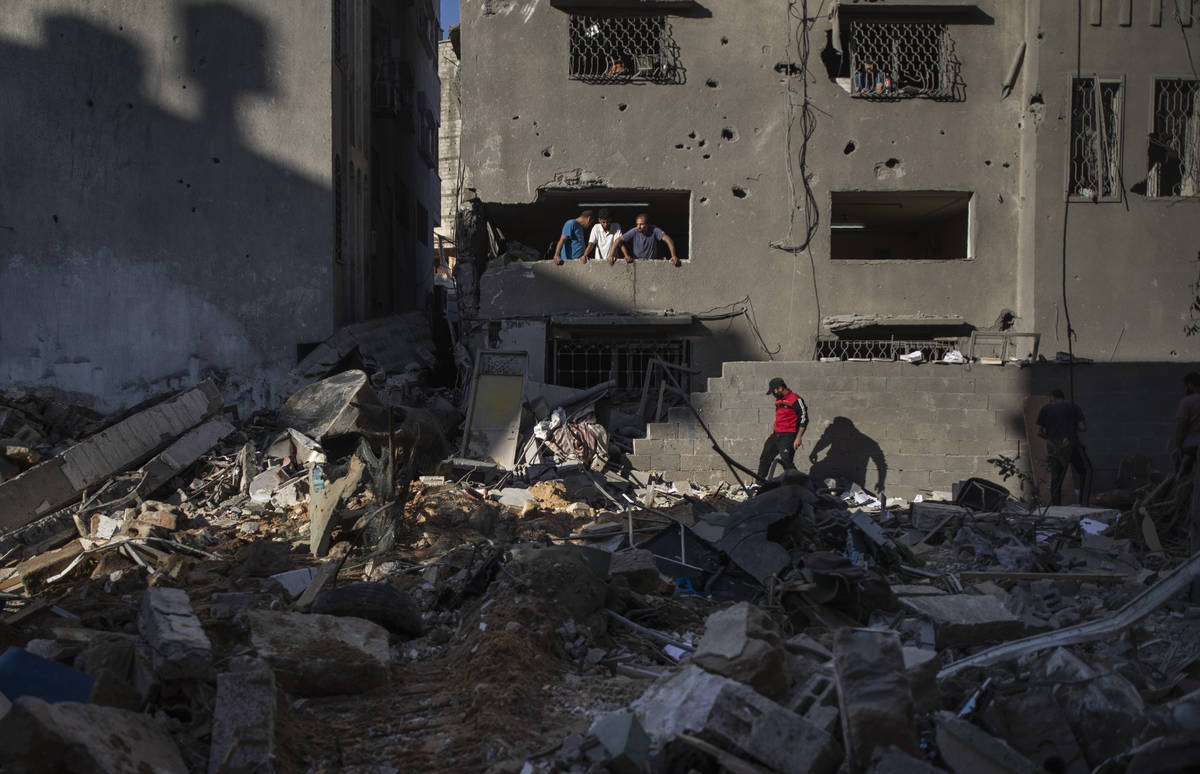 Palestinians look at destruction caused by Israeli air strikes that killed ten members of the A ...