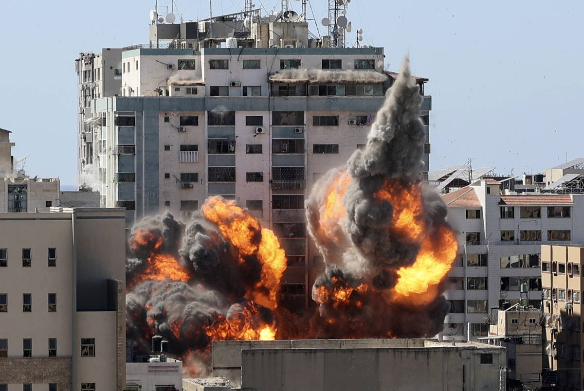 A ball of fire erupts from a building housing various international media, including The Associ ...
