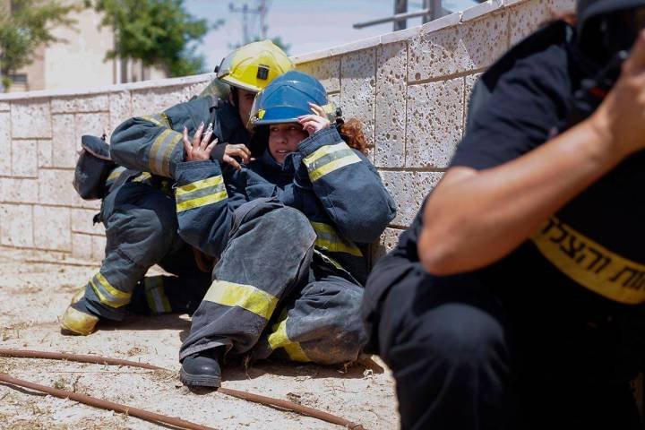 Israeli firefighters take cover as a siren sounds a warning of incoming rockets fired from the ...