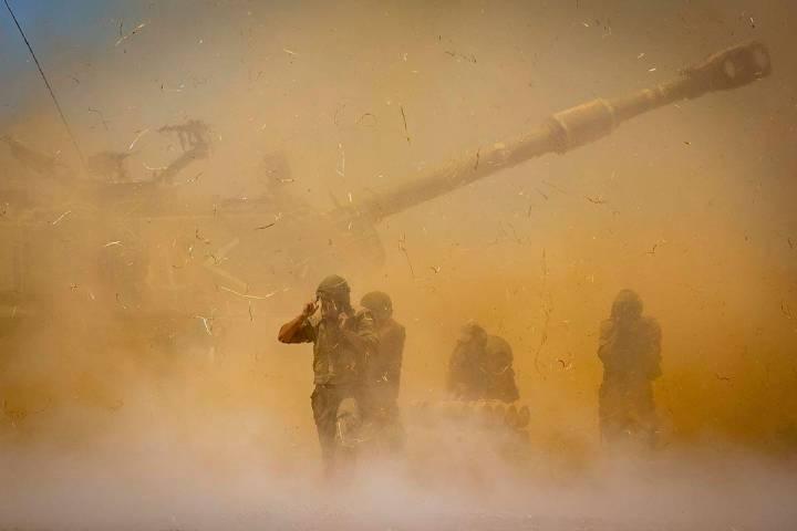 An Israeli artillery unit fires toward targets in Gaza Strip, at the Israeli Gaza border, Wedne ...