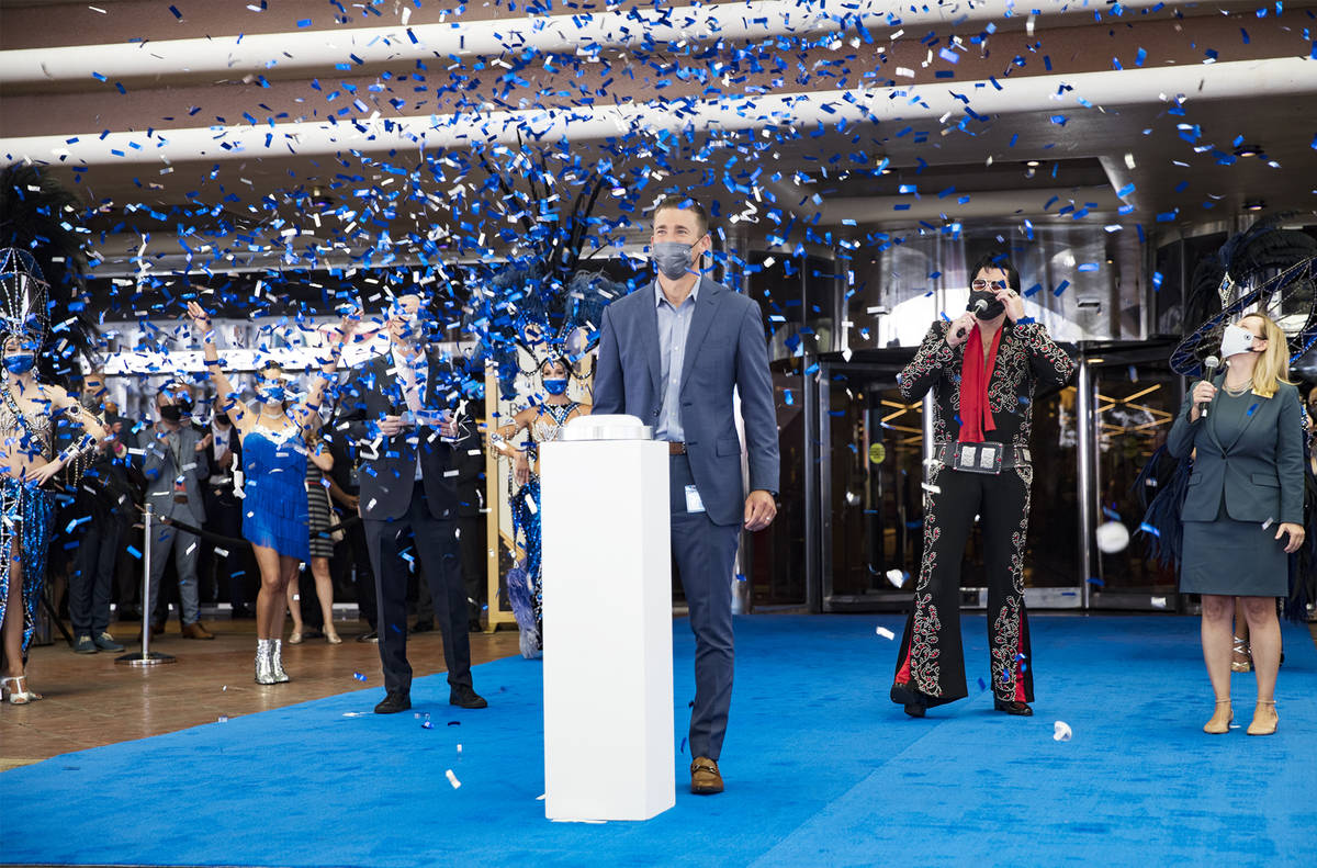 Anthony Carano, president and chief operating officer of Caesars Entertainment, presses a butto ...