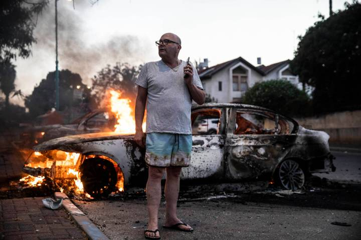 Jacob Simona stands by his burning car during clashes with Israeli Arabs and police in the Isra ...