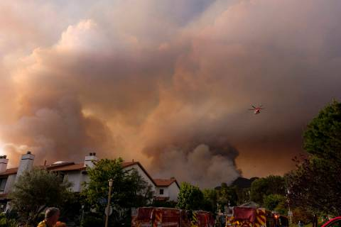 A firefighting helicopter drops water on a brush fire scorching at least 100 acres in the Pacif ...