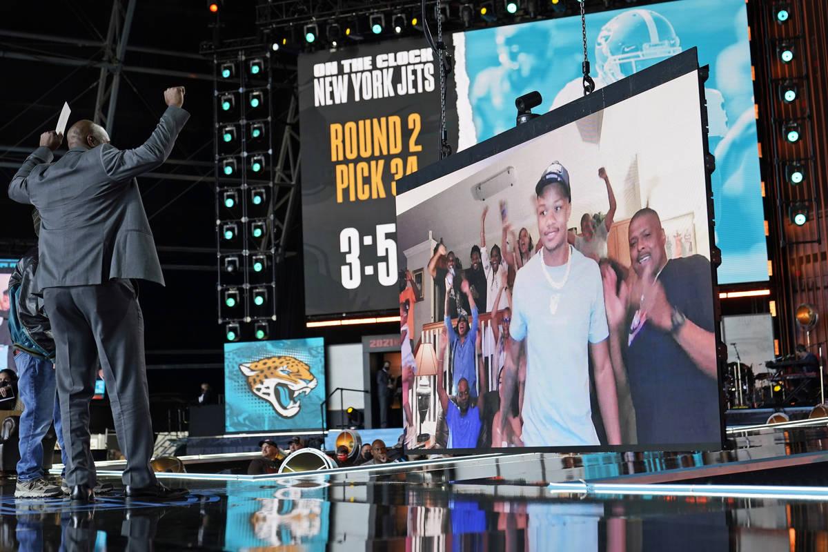 Former Jacksonville Jaguar Kevin Hardy raises his arms as an image of Georgia cornerback Tyson ...