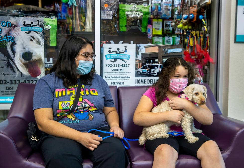 Arami Sanabria, left, and her sister Bella get to know their new adopted dog, Cream. (L.E. Baskow)