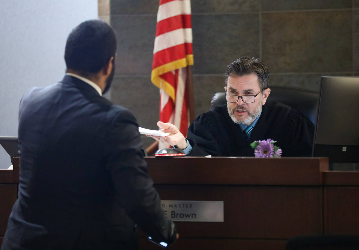 Attorney Christopher Storke hands documents to hearing master David Brown during his client&#x2 ...