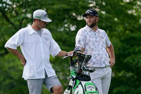 Jon Rahm talks with his caddie as he waits to hit on the 14th tee during the third round of the ...