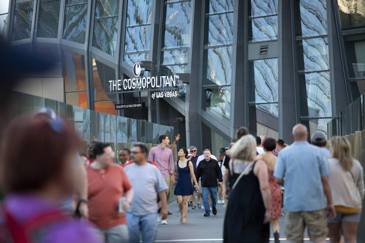 Visitors to the Las Vegas Strip cross a pedestrian bridge outside Cosmopolitan of Las Vegas on ...