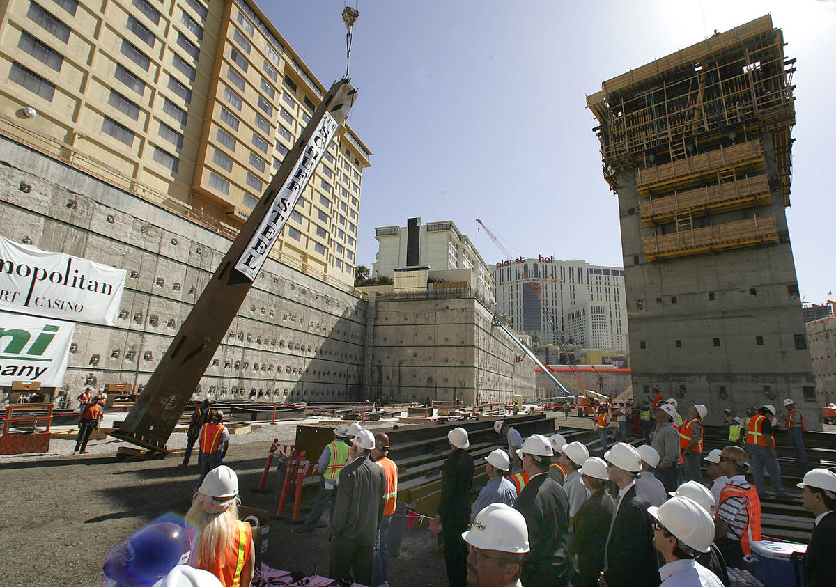 A steel column is hoisted into position as VIP guests and construction workers look on during a ...