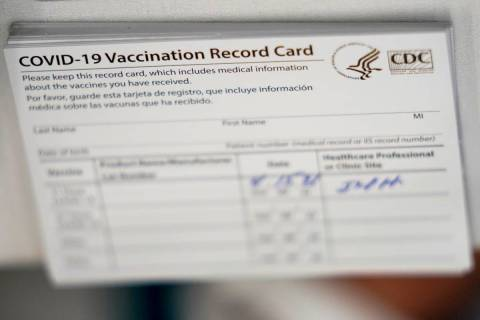 A stack of COVID-19 vaccination record cards are shown at the Christine E. Lynn Rehabilitation ...