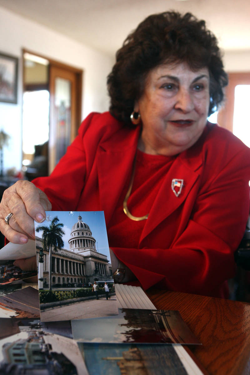 Liliam Lujan Hickey holds a photograph of the Capital Building in Havana, Cuba, while talking i ...
