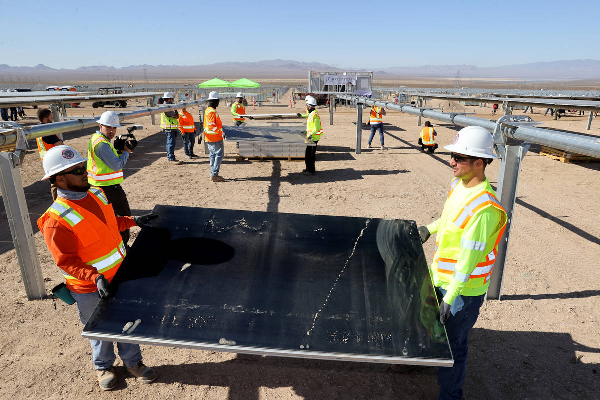 IBEW Local 357 workers, including Mark Contreras, left, and Chandler Higgins install modules at ...