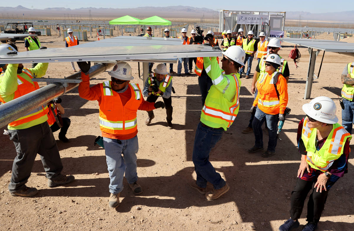 U.S. Energy Secretary Jennifer Granholm, right, watches IBEW Local 357 workers install modules ...