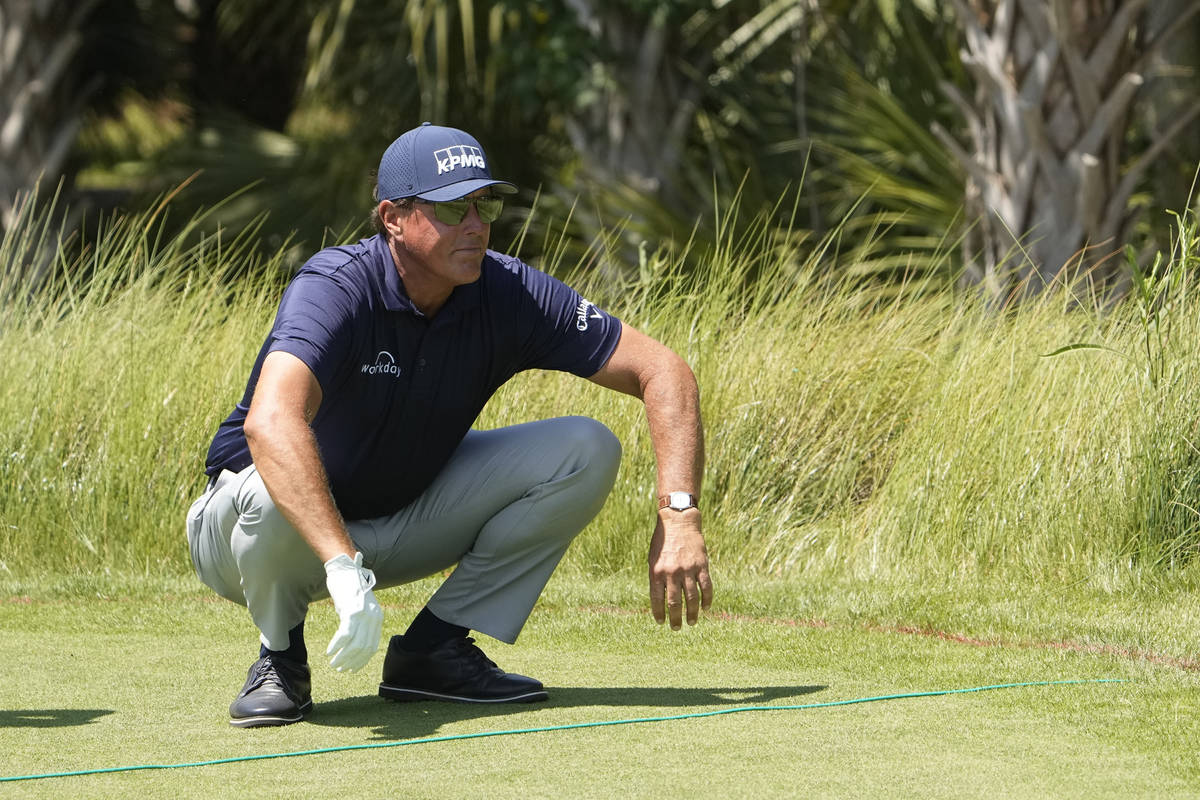 Phil Mickelson stretches before hitting off the second tee during the final round at the PGA Ch ...