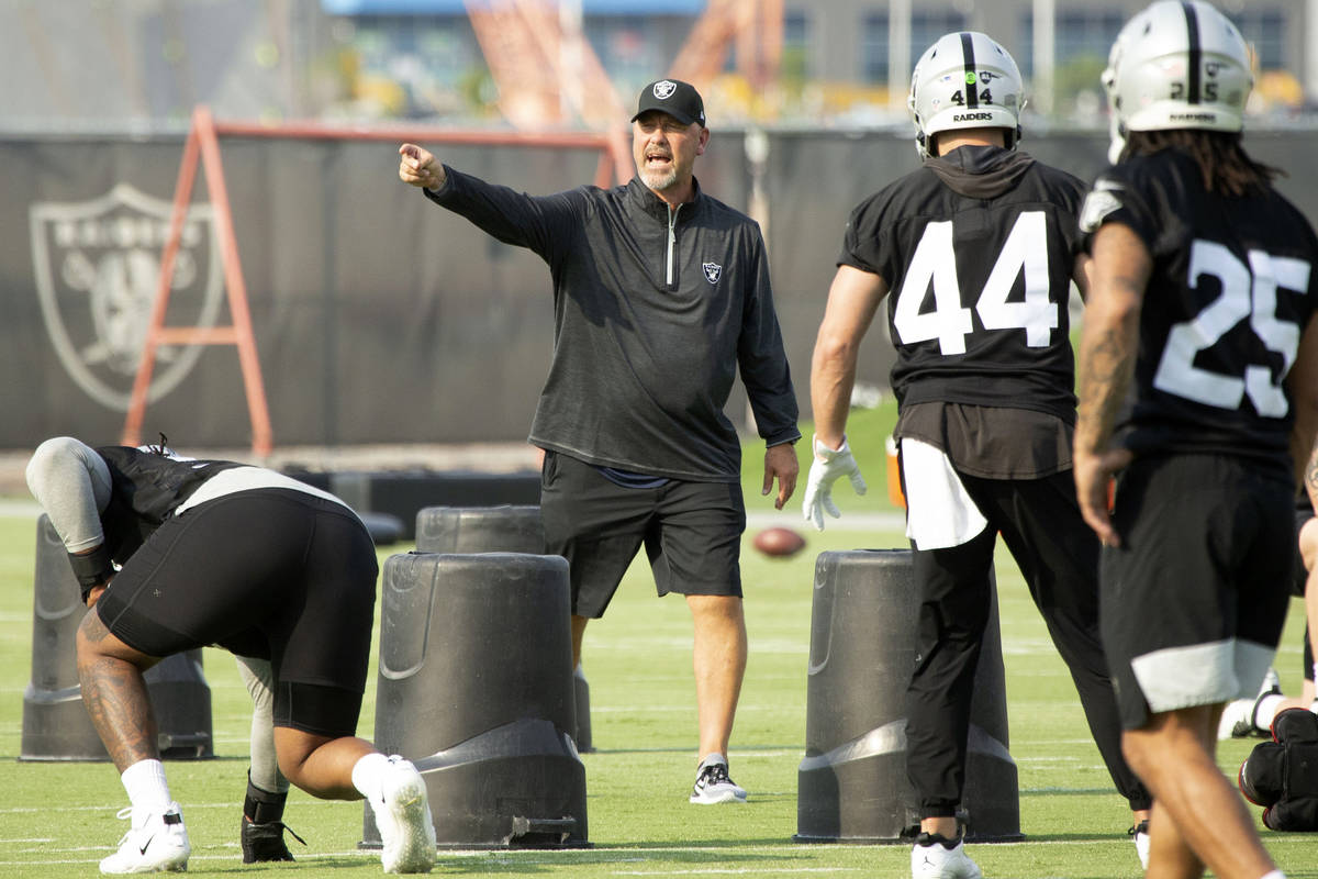 Raiders defensive coordinator Gus Bradley instructs defensive end Kendal Vickers (93) and lineb ...
