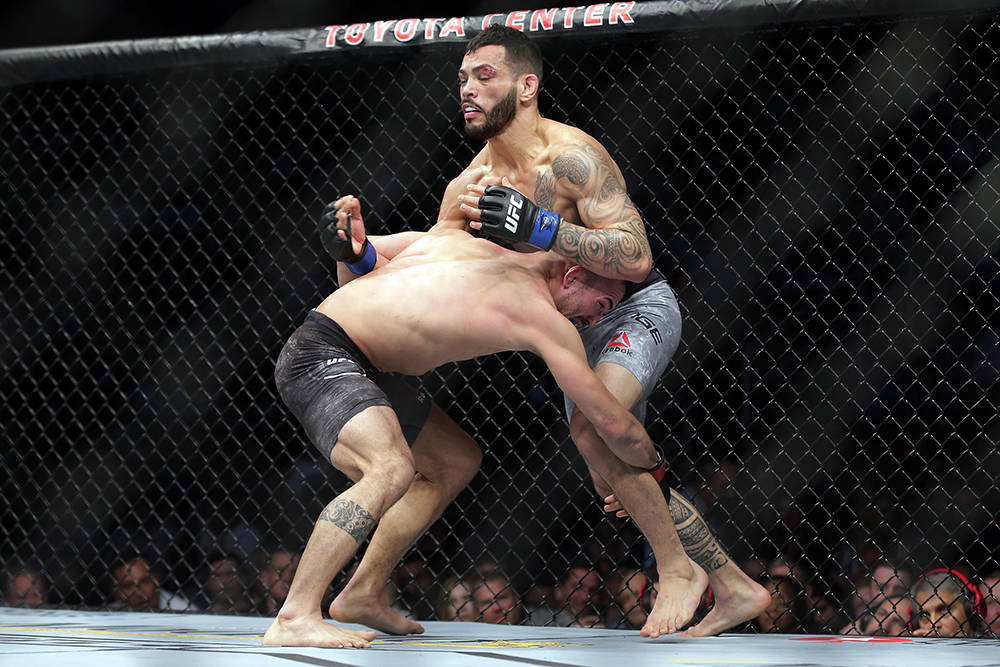 Mirsad Bektic, left, grabs the leg of Dan Ige during the first round of a featherweight mixed m ...