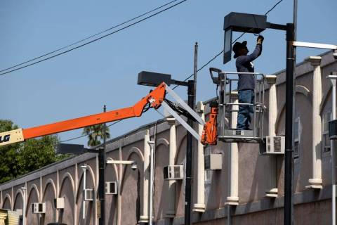A worker fixes a street lamp in the Van Nuys section of Los Angeles on Thursday, June 17, 2021. ...