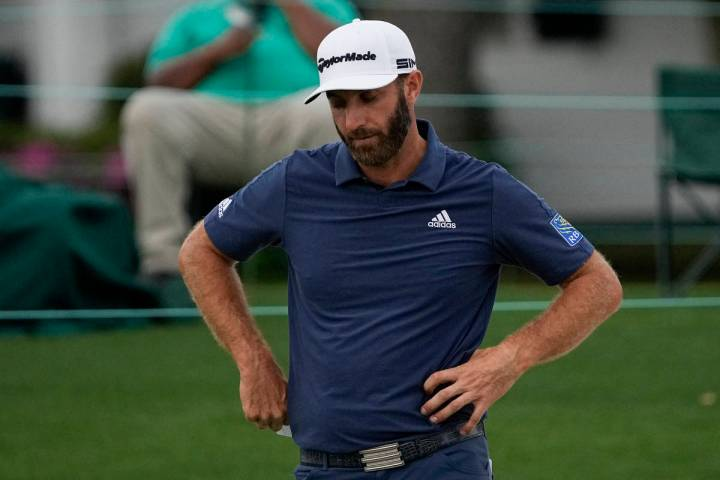 Dustin Johnson looks down after putting on the 18th hole during the second round of the Masters ...