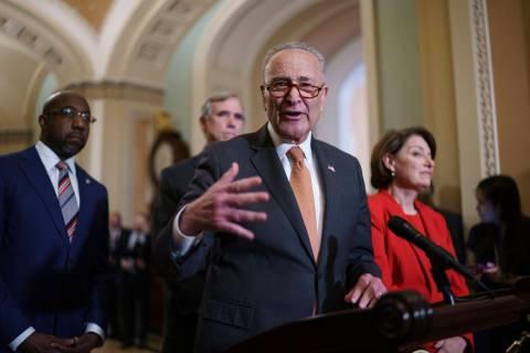 Senate Majority Leader Chuck Schumer, D-N.Y., flanked by Sen. Raphael Warnock, D-Ga., left, and ...