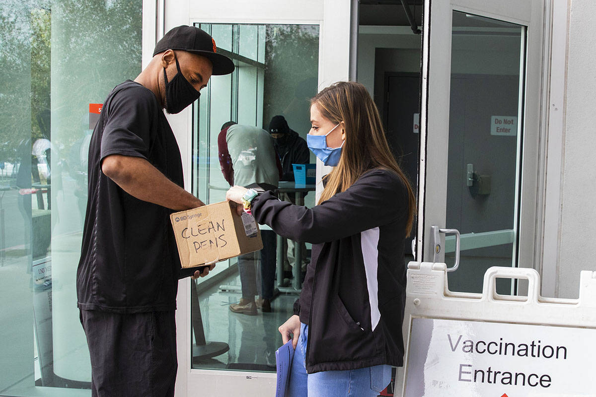 Ann Beck, right, a volunteer, hands out clean pens to a man who came to receive a COVID-19 vacc ...