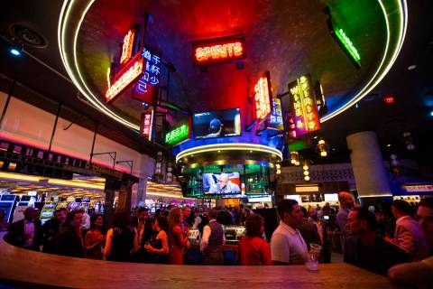 People mingle and drink cocktails by a bar at the Famous Foods Street Eats area during the open ...