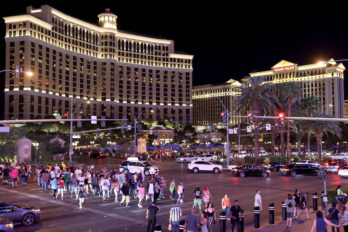 People walk between the Bellagio and Planet Hollywood Resort on the Strip in Las Vegas Friday, ...