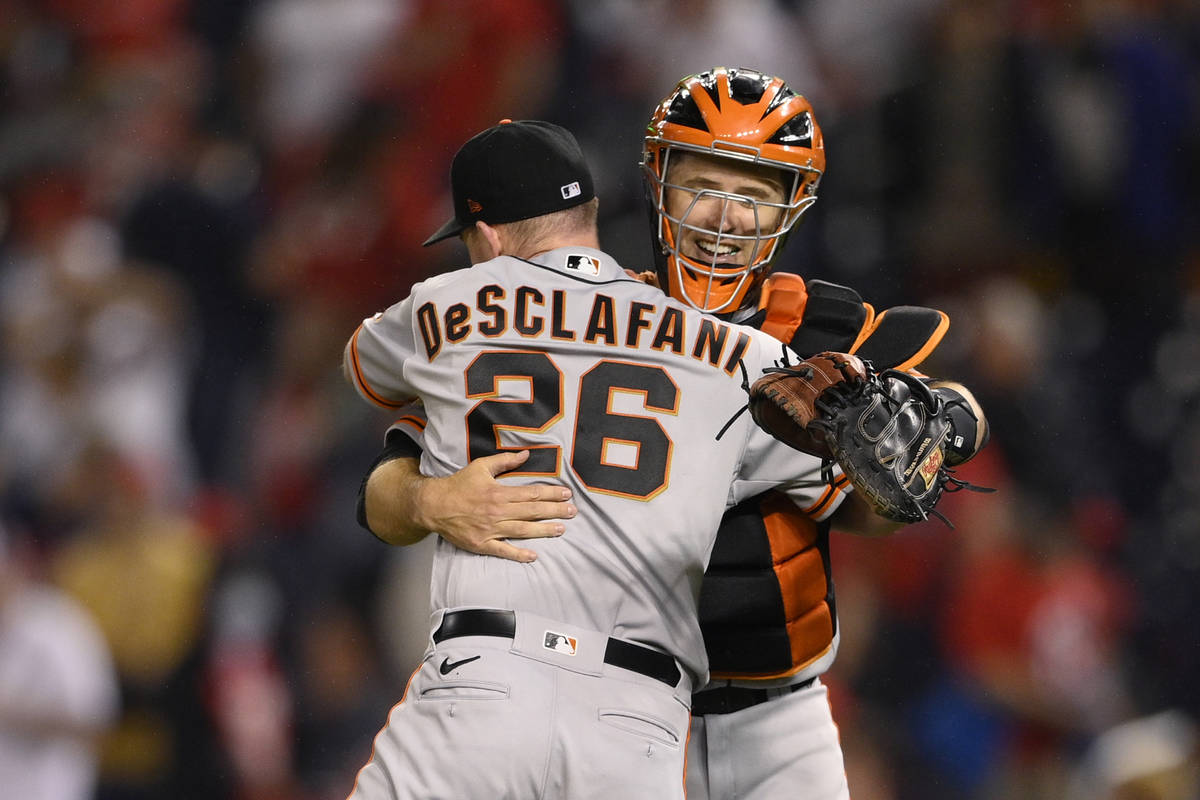 San Francisco Giants starting pitcher Anthony DeSclafani (26) and catcher Buster Posey, right, ...
