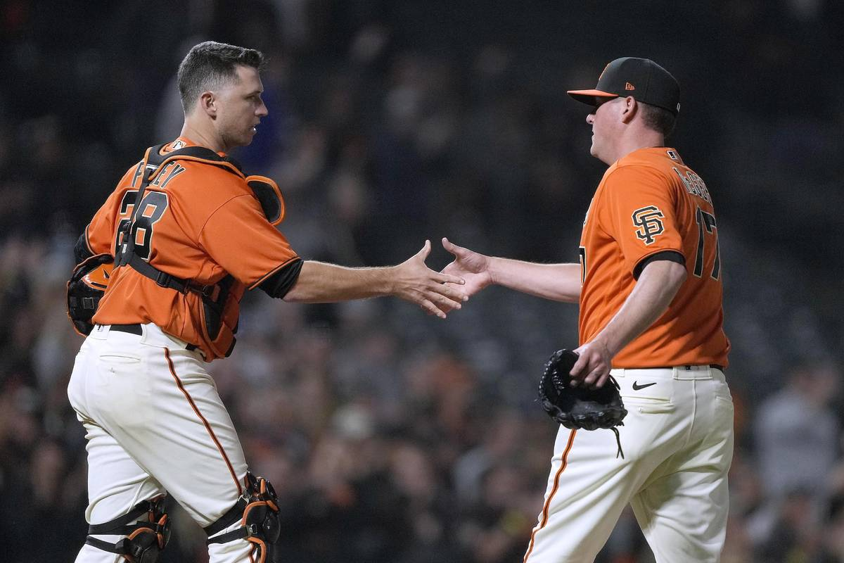 San Francisco Giants relief pitcher Jake McGee (17) shake hands with catcher Buster Posey after ...