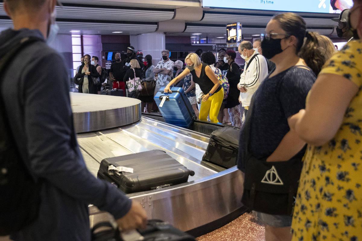 People wait for their baggage at McCarran International Airport Terminal 1 in Las Vegas, Friday ...