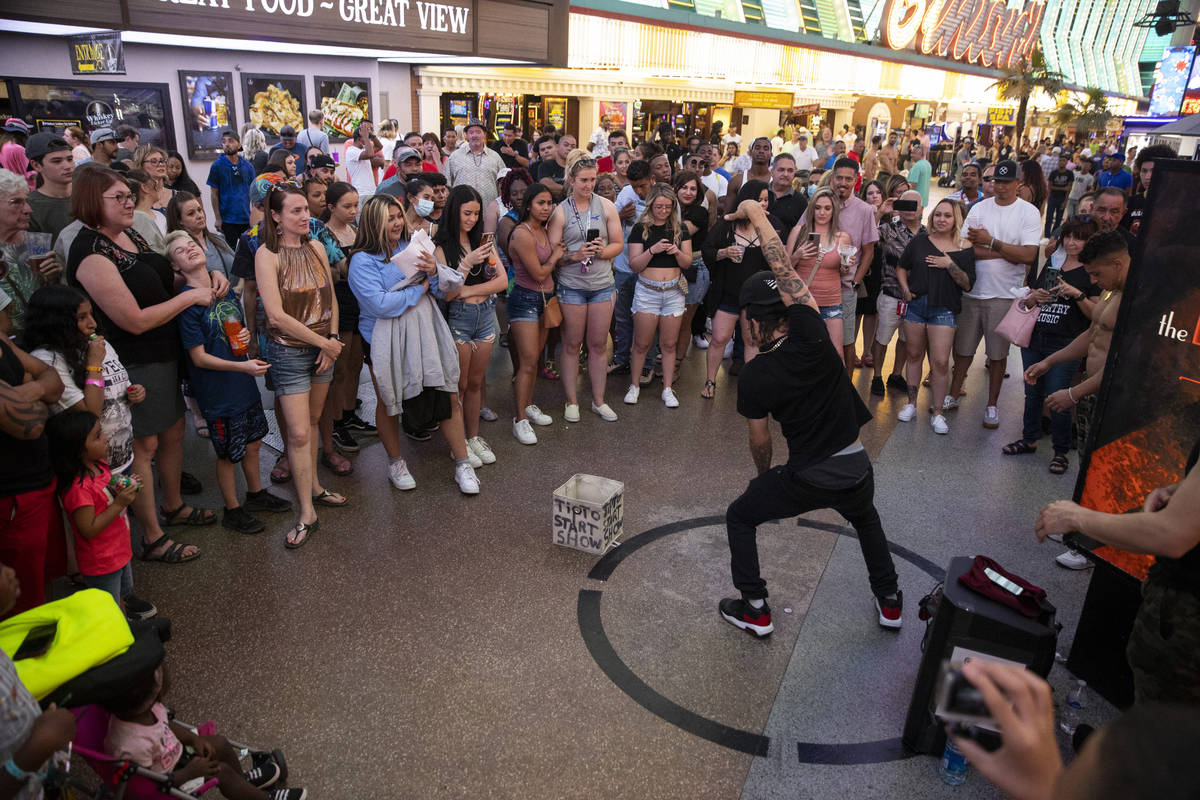 People watch a performer at the Fremont Street Experience in Las Vegas, Friday, July 2, 2021. ( ...