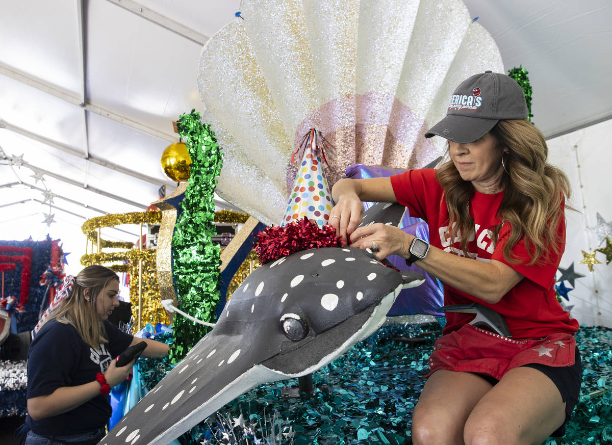 "Jordyn Doyle, left, and Elizabeth Engle, volunteers, decorate ""Undersea Jubilee"" float for the ..."