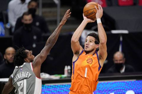 Phoenix Suns guard Devin Booker, right, shoots as Los Angeles Clippers guard Patrick Beverley d ...